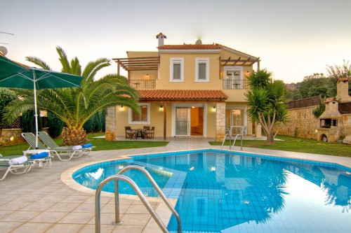 Outside the villa there is a swimming pool and a garden with lawns and ornamental plants